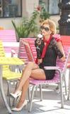 有一点黑礼服和红色围巾的时兴的夫人坐椅子在餐馆,室外射击在晴天 新金发碧眼的女人 免版税库存照片