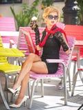 有一点黑礼服和红色围巾的时兴的夫人坐椅子在餐馆,室外射击在晴天 新金发碧眼的女人 免版税库存图片