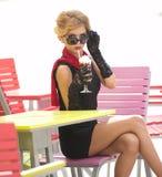 有一点黑礼服和红色围巾的时兴的夫人坐椅子在餐馆,室外射击在晴天 新金发碧眼的女人 库存图片