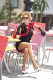 有一点黑礼服和红色围巾的时兴的夫人坐椅子在餐馆,室外射击在晴天 新金发碧眼的女人 免版税图库摄影