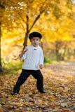 有一片大叶子的小男孩在公园 免版税库存照片