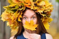 有一片枫叶的美丽的年轻深色的妇女在她的手上,花费时间在秋天公园 库存图片