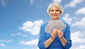 有一百美元金钱钞票的资深妇女 图库摄影