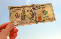 有一百美元钞票的手 免版税库存图片