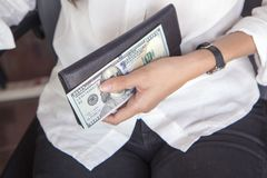 有一百美元钞票的黑皮革钱包在少妇 免版税库存图片