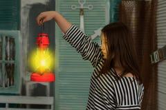有一盏被点燃的煤油灯的女孩在晚上在葡萄酒屋子 免版税图库摄影