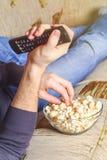 有一碗玉米花和一遥控的一个人在他的手上看在沙发的电视 免版税图库摄影