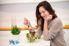 有一碗的困女孩沙拉在厨房里 图库摄影