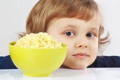有一碗的美丽的白肤金发的子项小米粥 库存图片