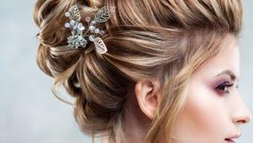 有一种典雅的高发型的年轻美丽的新娘 与辅助部件的婚礼发型在她的头发 图库摄影