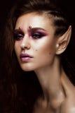 有一种创造性的发型辫子、艺术构成和矮子` s耳朵的深色的女孩 秀丽表面 免版税库存图片