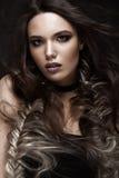 有一种创造性的发型辫子和黑暗的构成的深色的女孩 秀丽表面 库存图片
