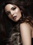 有一种创造性的发型辫子和黑暗的构成的深色的女孩 秀丽表面 库存照片