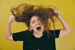 有一种奇怪的发型的恼怒的妇女 库存图片
