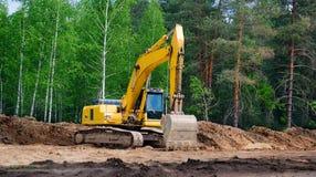 有一种履带牵引装置的黄色挖掘机在毛虫轨道,在高速公路的建筑的工作 库存照片