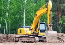 有一种履带牵引装置的黄色挖掘机在毛虫轨道,在高速公路的建筑的工作 免版税库存照片