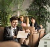 有一种数字式片剂的企业家新手坐在一个现代办公室的大厅的长沙发 免版税库存图片