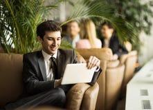 有一种数字式片剂的企业家新手坐在一个现代办公室的大厅的长沙发 免版税图库摄影