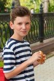 有一种时兴的发型和汉堡的年轻微笑的男孩 免版税库存图片