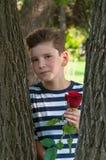 有一种时兴的发型和玫瑰的一个年轻浪漫男孩 免版税图库摄影