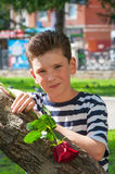 有一种时兴的发型和玫瑰的一个年轻浪漫男孩 免版税库存图片