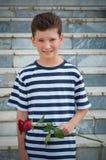 有一种时兴的发型和玫瑰的一个年轻浪漫男孩 库存图片