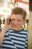 有一种时兴的发型的年轻微笑的男孩在步行 免版税库存照片