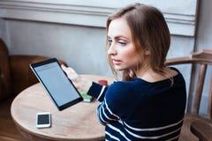 有一种片剂的一名妇女在咖啡馆 在想法失去的一个女孩 都市偶然教的样式和放松在咖啡馆 免版税库存图片