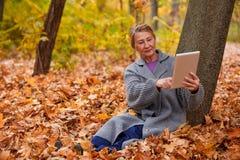 有一种片剂的一名成熟妇女在她的手上坐在叶子的一棵树下 外部在秋天公园 库存照片