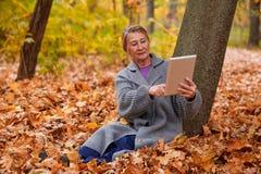 有一种片剂的一名成熟妇女在她的手和接触上它与她的手指坐在树下 外部在秋天公园 免版税库存图片