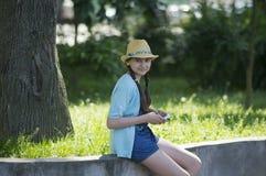 有一种片剂的女孩在城市公园 免版税库存图片