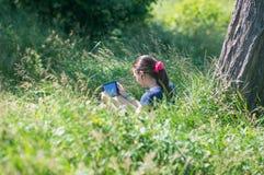 有一种片剂的女孩在耳机 免版税库存照片