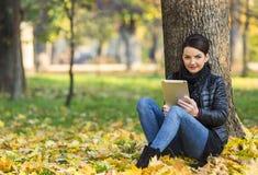 有一种片剂的妇女在一个森林里在秋天 免版税库存照片