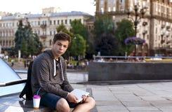有一种片剂的年轻人在一个大城市的街道上 图库摄影