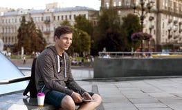 有一种片剂的年轻人在一个大城市的街道上 库存图片