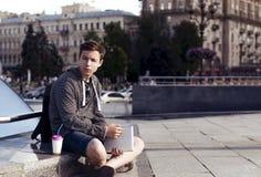 有一种片剂的年轻人在一个大城市的街道上 免版税库存图片