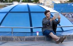 有一种片剂的年轻人在一个蓝色玻璃圆顶附近 图库摄影