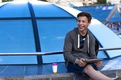 有一种片剂的年轻人在一个蓝色玻璃圆顶附近 库存照片