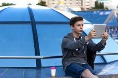 有一种片剂的年轻人在一个蓝色玻璃圆顶附近 免版税图库摄影