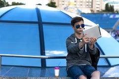 有一种片剂的年轻人在一个蓝色玻璃圆顶附近 免版税库存图片