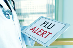有一种片剂的医生有文本流感戒备的 免版税库存图片