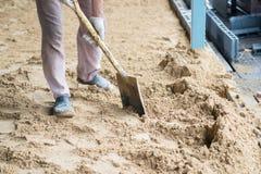 有一种铁锹运转的挖掘机的工作者在建筑建筑工地 免版税库存图片
