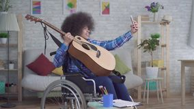 有一种非洲的发型的失去能力的非裔美国人的妇女在轮椅采取与一把声学吉他的一selfie 股票视频