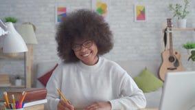 有一种非洲的发型的画象非裔美国人的学生妇女微笑和看照相机的 股票录像