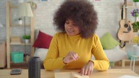 有一种非洲的发型的非洲妇女享用读书的声音助理在桌上 影视素材