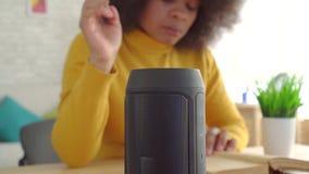 有一种非洲的发型的非洲妇女享用读书的声音助理在桌关闭  股票视频