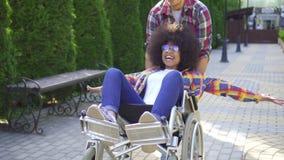 有一种非洲的发型的非洲妇女残疾在一个轮椅在步行的公园与有的朋友乐趣关闭 股票录像