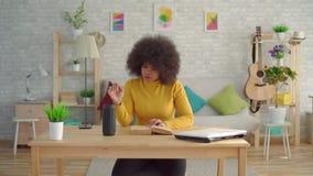 有一种非洲的发型的黑人妇女享用读书的声音助理在桌上 股票视频