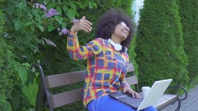 有一种非洲的发型的黑人美国妇女使用愉快一台的膝上型计算机赢得 影视素材