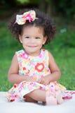 有一种非洲的发型的小女孩坐草 免版税库存图片